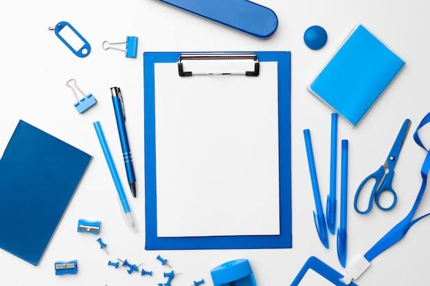 Artigos de papelaria azul da cor ajustados como teste padrão com espaço da cópia na configuração branca, lisa.