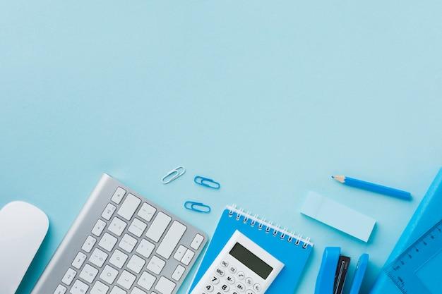 Artigos de papelaria azul do escritório com espaço da cópia