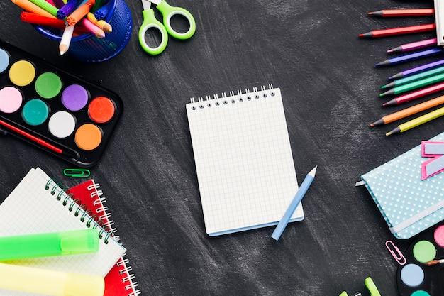 Artigos de papelaria brilhante em confusão ao redor do caderno branco sobre fundo cinza