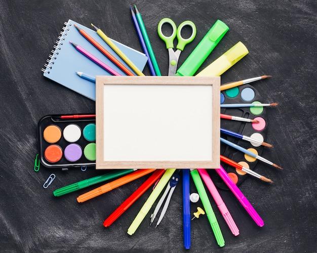 Artigos de papelaria btight e aquarela em torno do quadro em branco