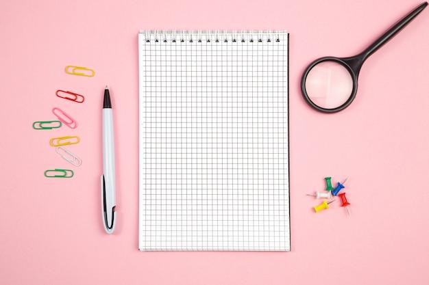 Artigos de papelaria, caderno de papel com caneta e lupa sobre fundo rosa isolado. vista do topo. configuração plana. brincar