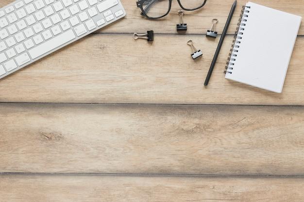 Artigos de papelaria colocados perto de teclado e óculos na mesa de madeira