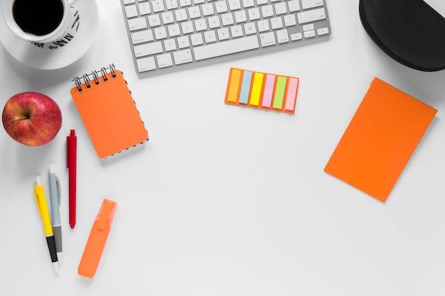 Artigos de papelaria coloridos com xícara de café; maçã e teclado na mesa branca