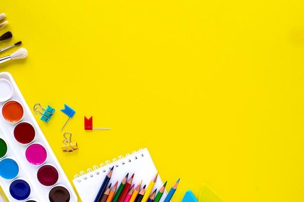 Artigos de papelaria coloridos da escola em fundo amarelo com copyspace.