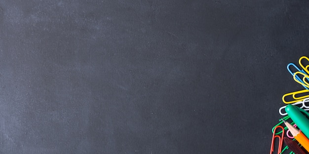 Artigos de papelaria coloridos de volta ao conceito de escola no escuro
