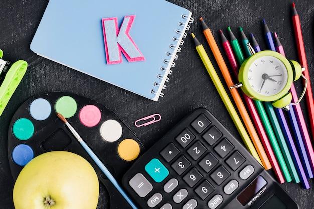 Artigos de papelaria coloridos desarrumado, maçã, calculadora no fundo escuro