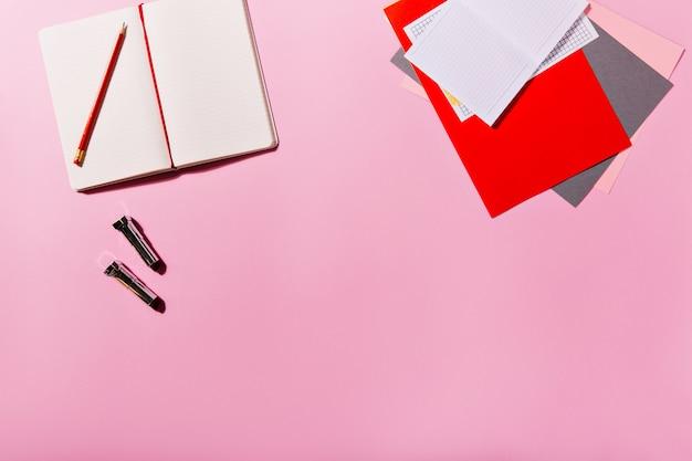 Artigos de papelaria coloridos e cadernos abertos estão ao lado de batons na parede rosa