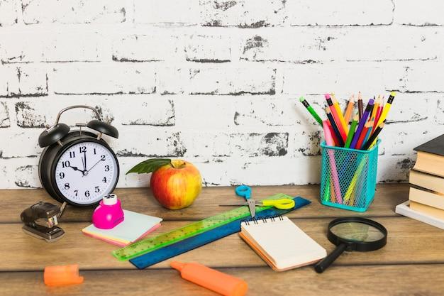 Artigos de papelaria coloridos e maçã colocados de forma aleatória