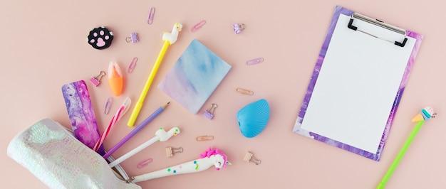 Artigos de papelaria da escola com caneta de unicórnio, lápis lama em um fundo rosa. volta às aulas escrivaninha criativa com artigos de papelaria kawaii, flatlay e vista superior. pano de fundo panorâmico