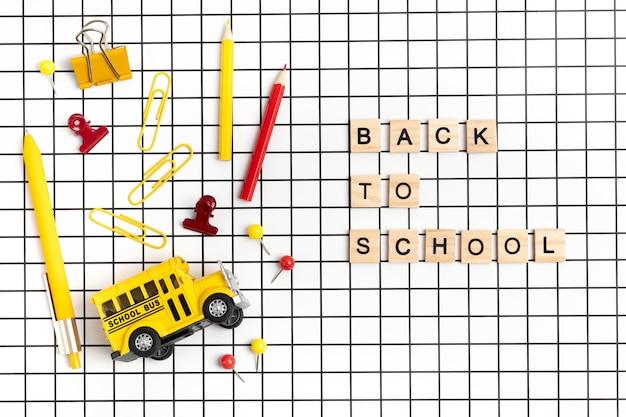 Artigos de papelaria da escola em fundo branco quadriculado. de volta à ideia de escola, conceito de estudo. vista superior, configuração plana