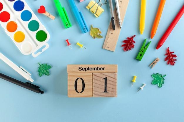 Artigos de papelaria da escola em um fundo azul. calendário de madeira 1 de setembro. conceito do dia do conhecimento.