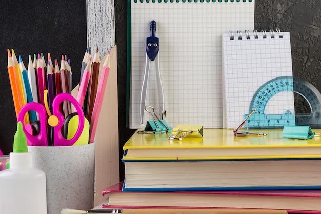 Artigos de papelaria da escola em uma mesa na frente do quadro-negro,