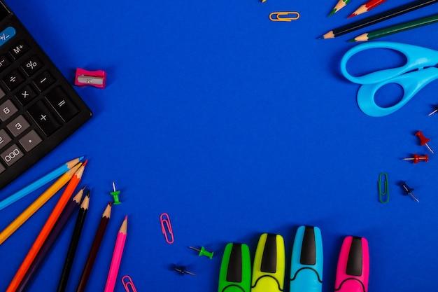 Artigos de papelaria da escola ou do escritório no fundo azul. de volta à escola. moldura, copie o espaço. suprimentos