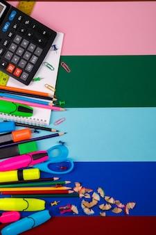 Artigos de papelaria da escola ou do escritório no fundo colorido. de volta à escola. moldura, copie o espaço.