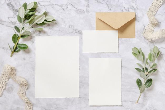 Artigos de papelaria de casamento com envelope colocado sobre uma mesa de mármore decorada com fitas e galhos de eucalipto. cena de mock-up com cartões de papel em branco. postura plana feminina