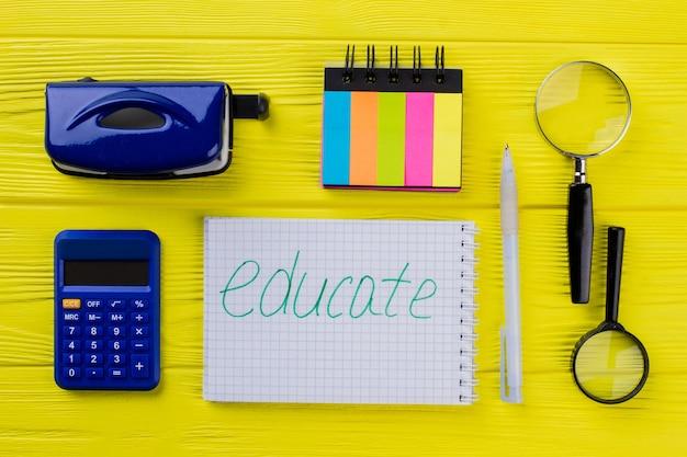 Artigos de papelaria de educação esfolam leigos. bloco de notas de vista superior com calculadora e lupa em madeira amarela.