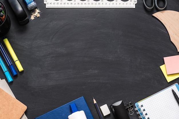 Artigos de papelaria de escritório espalhados na superfície do quadro-negro