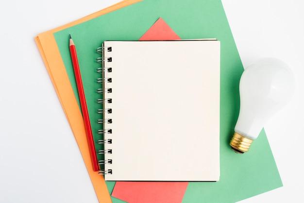 Artigos de papelaria de ofício e lâmpada branca sobre a superfície branca