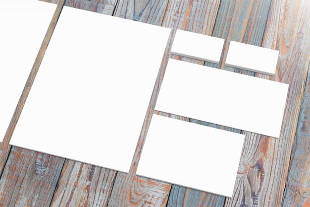 Artigos de papelaria de papel em branco na mesa de madeira