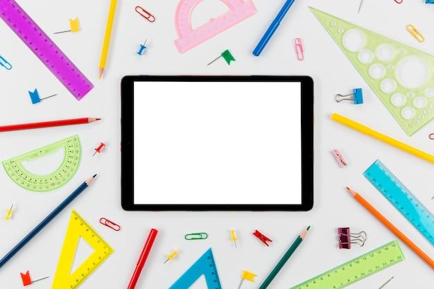 Artigos de papelaria de vista superior com tablet em cima da mesa