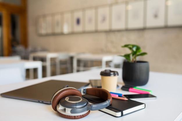 Artigos de papelaria diferentes e legais dispostos em uma mesa branca em um escritório colaborativo