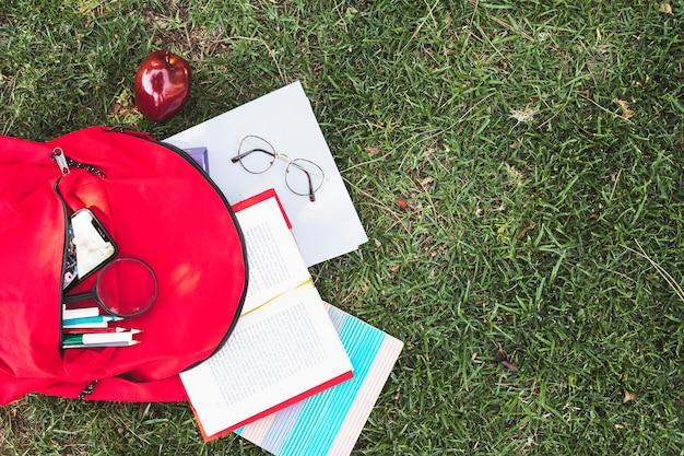 Artigos de papelaria dispersos da mochila vermelha na grama