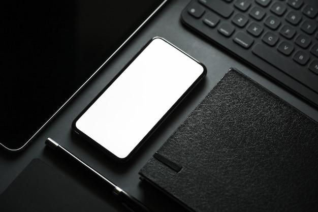 Artigos de papelaria do escritório com o telefone esperto móvel da tela vazia no fundo escuro.
