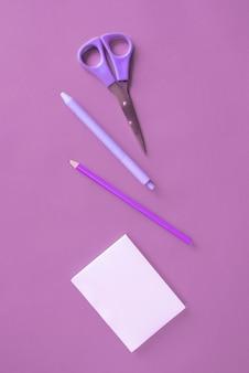 Artigos de papelaria do escritório na superfície roxa