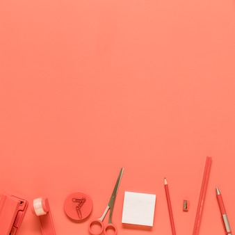 Artigos de papelaria do escritório no fundo vermelho