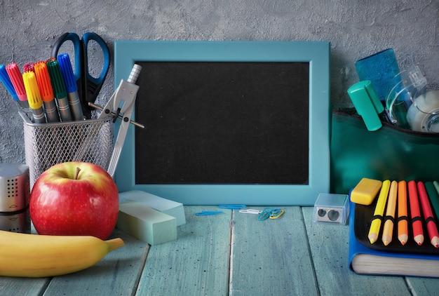 Artigos de papelaria e frutas em uma mesa na frente do quadro-negro com espaço de texto