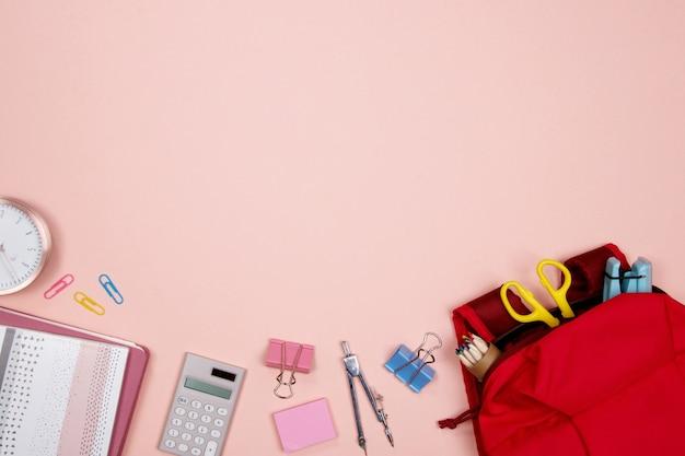 Artigos de papelaria e materiais de escritório no fundo cor-de-rosa. lay plana. volta ao conceito de escola.