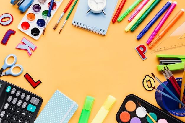 Artigos de papelaria e material de escritório colocados na mesa laranja