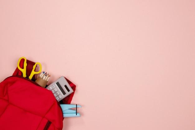 Artigos de papelaria e material de escritório no fundo rosa
