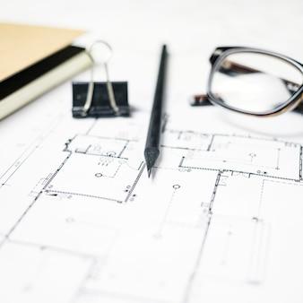 Artigos de papelaria e óculos deitado no blueprint