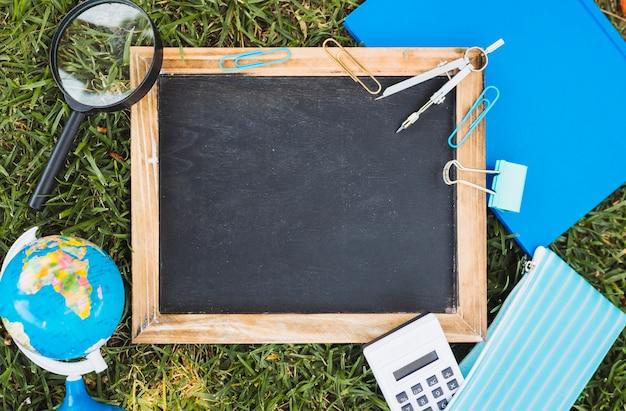 Artigos de papelaria e quadro de giz no gramado verde