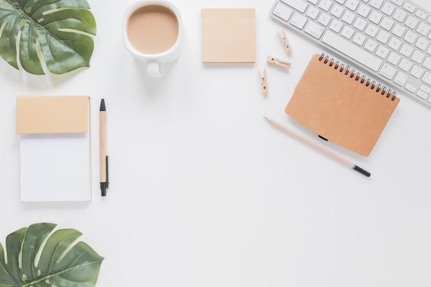 Artigos de papelaria e teclado na mesa branca com folhas verdes e xícara de café