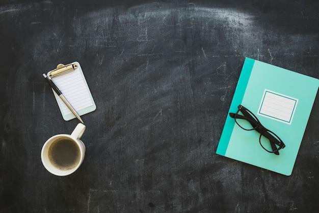 Artigos de papelaria e xícara de café no quadro-negro