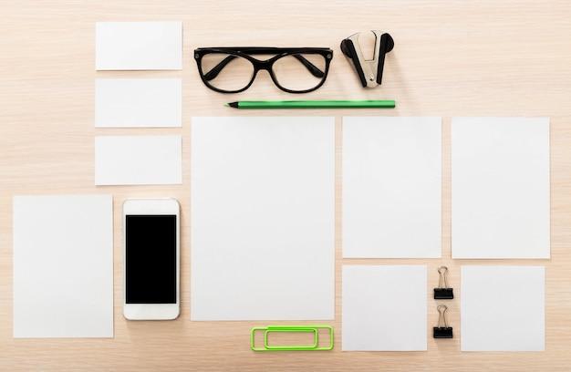 Artigos de papelaria em branco com óculos na mesa de madeira clara, vista superior