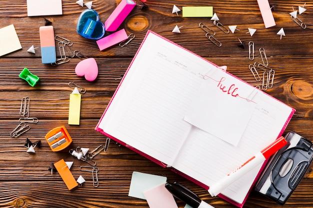 Artigos de papelaria em torno do caderno aberto com nota