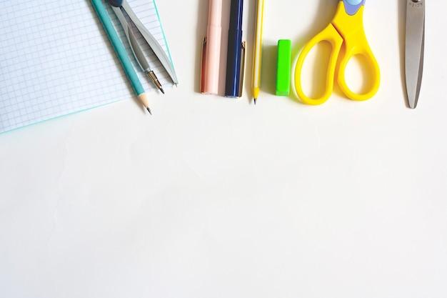 Artigos de papelaria em um fundo branco, canetas para cadernos, lápis, bússolas, borracha e tesoura, disposição plana, espaço de cópia