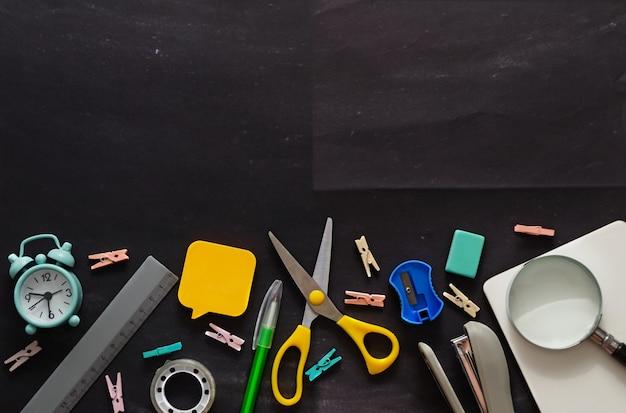 Artigos de papelaria em uma mesa de grafite surrada com restos de giz de volta ao modelo de conceito da escola para ...