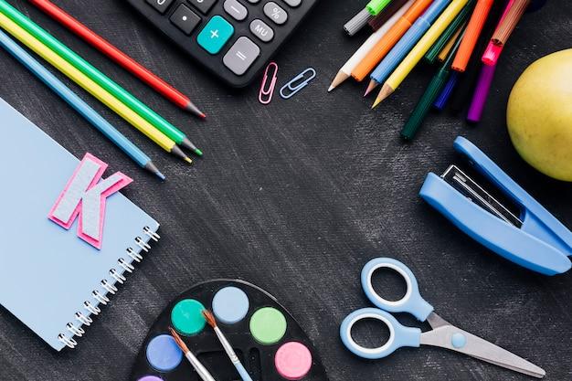 Artigos de papelaria escolar colorido espalhados na lousa