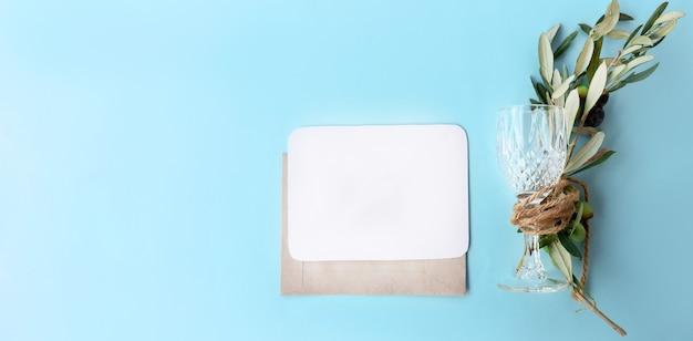 Artigos de papelaria femininos, cena de mock-up da área de trabalho. cartão horizontal em branco e envelope de ofício com ramo de oliveira e vidro de videira embrulhados juntos. fundo azul. camada plana, vista superior.
