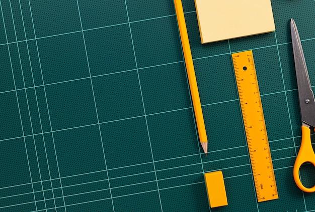 Artigos de papelaria laranja e tapete verde de corte close-up de imagens