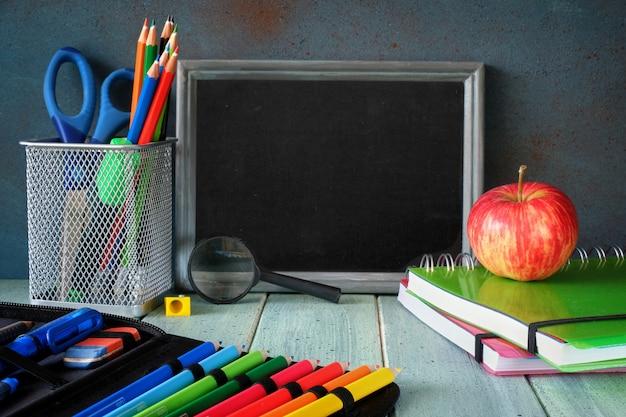 Artigos de papelaria, maçã e banana em uma mesa de madeira na frente do quadro-negro com espaço de texto