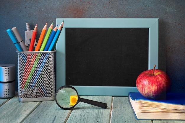 Artigos de papelaria, maçã e lupa na mesa de madeira na frente do quadro-negro com espaço de texto