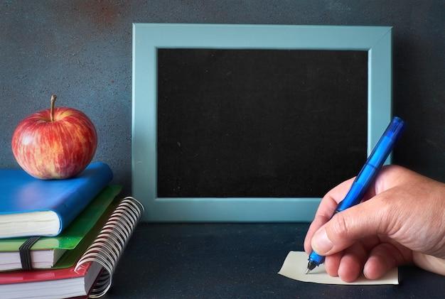 Artigos de papelaria, maçã e mão escrevendo uma nota sobre uma mesa de madeira na frente do quadro-negro com espaço de texto