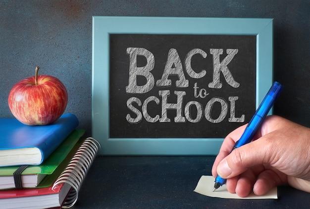 Artigos de papelaria, maçã e mão escrevendo uma nota sobre uma mesa de madeira na frente do quadro-negro com texto