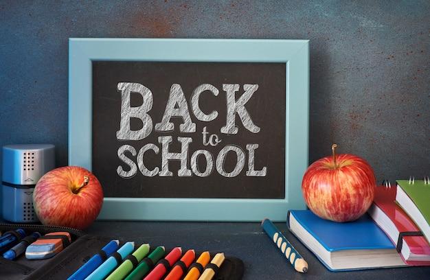Artigos de papelaria, maçãs e livros na mesa de madeira na frente do quadro-negro com texto