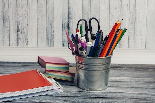 Artigos de papelaria, mesa de madeira, itens de escola e escritório